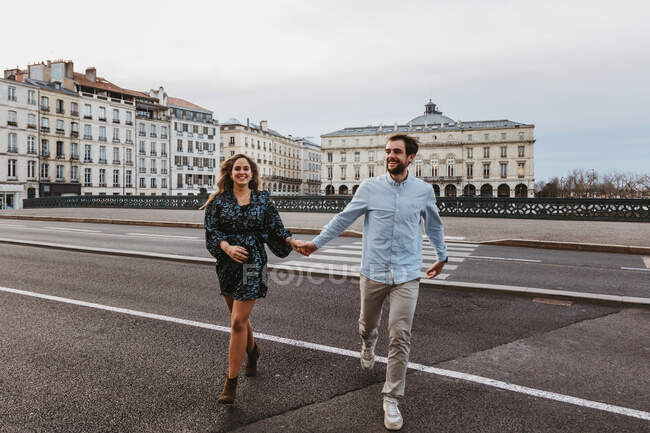 Feliz pareja romántica joven con ropa elegante riendo y tomados de la mano mientras cruzan el puente con edificios históricos en el fondo durante el recorrido por la ciudad en Bayona en Francia - foto de stock