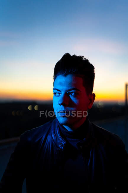 Serious young male with stylish haircut wearing black leather jacket looking away while standing on street against dark sunset sky — Stock Photo
