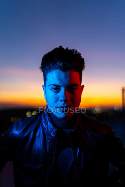 Serious young male with stylish haircut wearing black leather jacket looking at camera while standing on street against dark sunset sky — Stock Photo