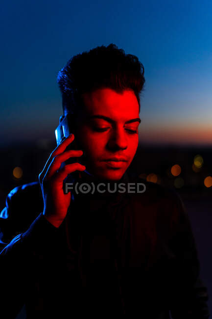 Homme moderne sérieux en veste noire parlant sur smartphone tout en se tenant debout dans la lumière rouge et bleue regardant vers le bas dans la rue avec un ciel bleu foncé en arrière-plan — Photo de stock