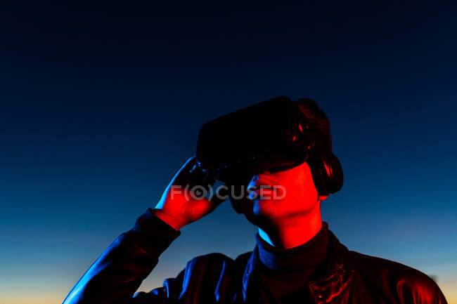 Modern male with VR headset exploring virtual world while standing in red neon light on street against dark sunset sky — Stock Photo