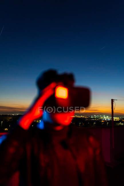 Hombre moderno con auriculares VR que exploran el mundo virtual mientras está de pie en la luz de neón roja en la calle contra el cielo oscuro atardecer - foto de stock