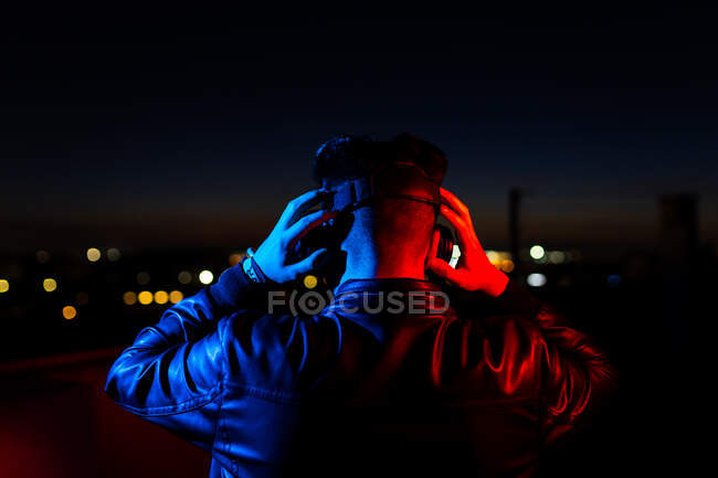 Back view of anonymous male in black leather jacket and virtual reality goggles standing on dark street against night sky with city lights in background — Stock Photo