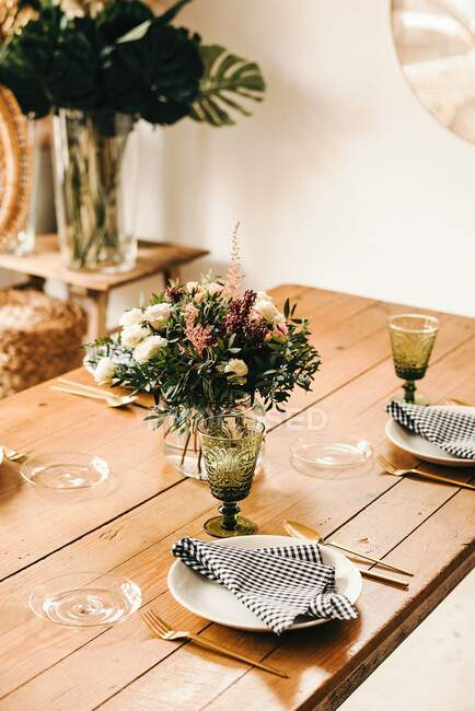 Strauß aus verschiedenen Blumen und grünen Pflanzenzweigen in einer Vase mit Wasser auf einem Holztisch für eine Mahlzeit — Stockfoto