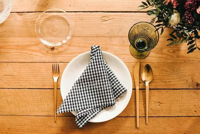 Von oben gedeckter Holztisch für eine Mahlzeit mit Teller, Besteck, Glas und Serviette in der Nähe von schönem Blumenstrauß mit grünen Pflanzenzweigen in der Vase — Stockfoto