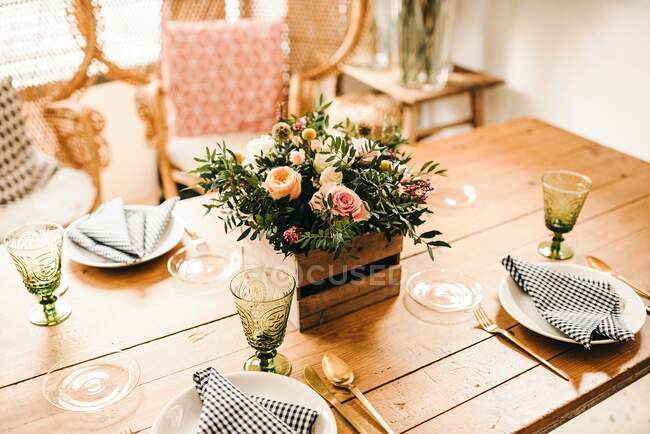 From above bouquet of miscellaneous flowers and green plant twigs in a wooden box on a timber table set for a meal with beautiful designed rattan chair on the background — Stock Photo