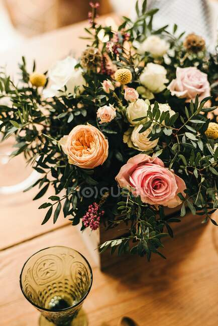 From above bouquet of miscellaneous flowers and green plant twigs in a wooden box on a timber table set for a meal — Stock Photo