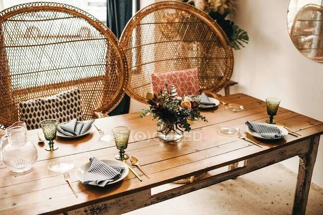D'en haut bouquet de fleurs diverses et de brindilles de plantes vertes dans un vase avec de l'eau sur une table en bois pour un repas avec belle chaise en rotin conçu sur le fond — Photo de stock