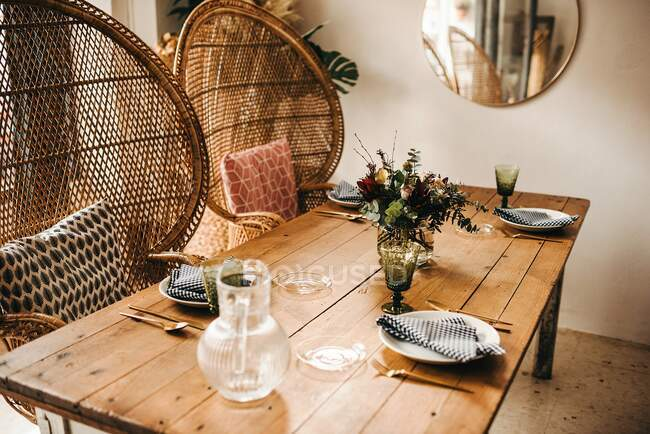 From above bouquet of miscellaneous flowers and green plant twigs in vase with water on a wooden table set for a meal with beautiful designed rattan chair on the background — Stock Photo