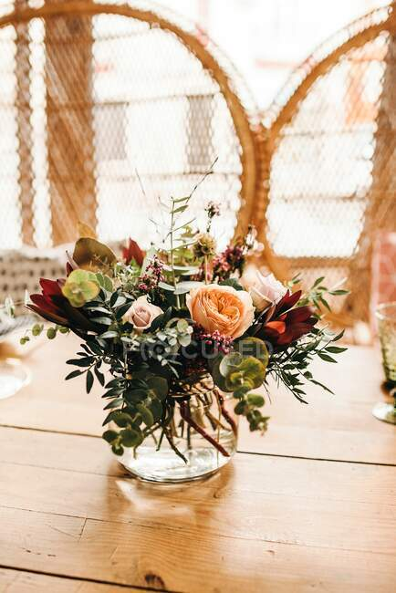 Bouquet of miscellaneous flowers and green plant twigs in vase with water on a wooden table set for a meal with beautiful designed rattan chair on the background — Stock Photo