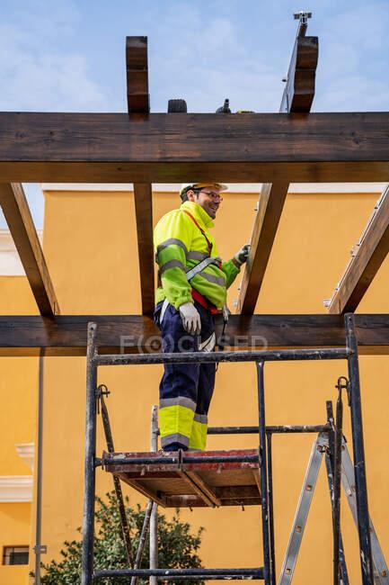 Dal basso vista laterale di tecnico maschile in abbigliamento da lavoro in piedi su ponteggi e preparazione per l'installazione di pannello solare su costruzione in legno — Foto stock