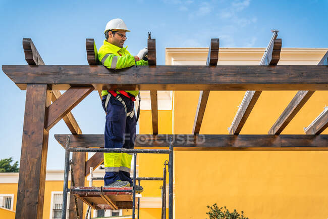 From below side view of male technician in work wear standing on scaffolding and preparing for installation of solar panel on wooden construction — Stock Photo