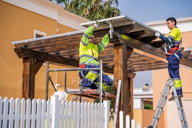 Group of workers in uniform and helmets installing photovoltaic panels on roof of wooden construction near house — Stock Photo