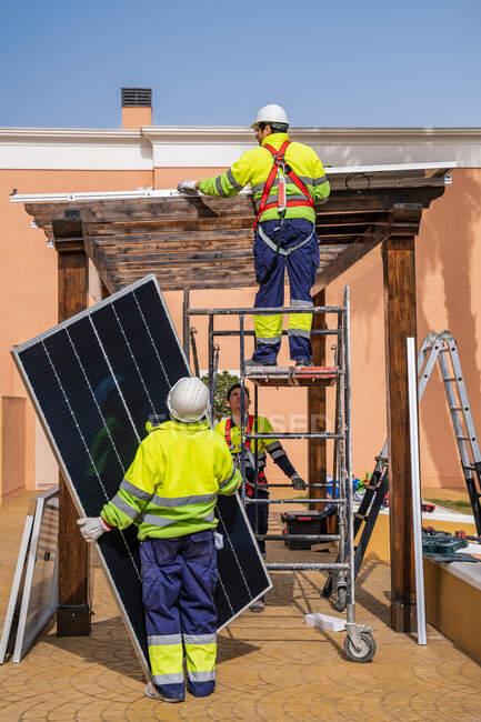 Група робітників у формі й шоломах встановлюють фотогальванічні панелі на даху дерев