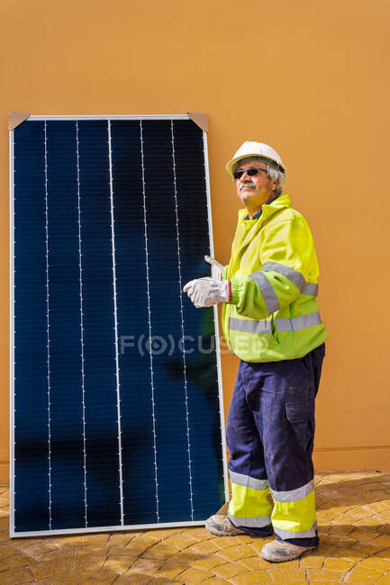 Side view of mature experienced male technician in uniform and helmet standing with solar panel near yellow building while working on installation of renewable energy system — Stock Photo