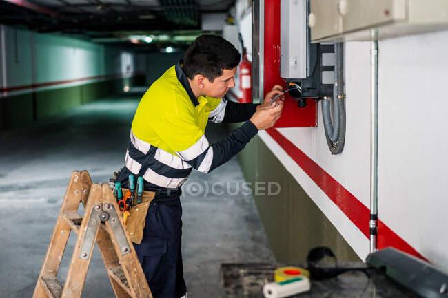 Vue latérale du jeune technicien masculin professionnel avec des outils électriques réparant et vérifiant l'équipement tout en travaillant dans le bâtiment — Photo de stock