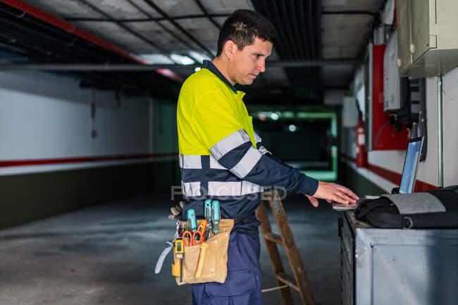 Seitenansicht des Fachmanns Ingenieur in Uniform mit Gadgets bei der Untersuchung von elektrischen Geräten in modernen Gebäuden — Stockfoto