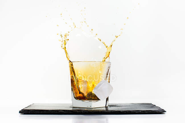 Glass of yellow cold drink with falling ice cube and splashes placed on black slate board on white background — Stock Photo