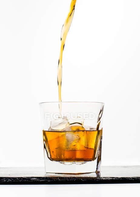 Склянка жовтого холодного напою з крижаним кубом і бризки розміщені на чорній дошці на білому тлі. — стокове фото