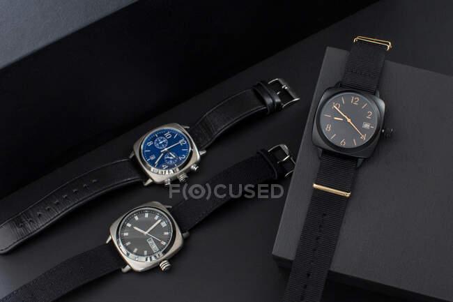 Desde arriba conjunto de modernos relojes de pulsera elegantes para hombres con diferentes esferas y pulseras de cuero negro - foto de stock