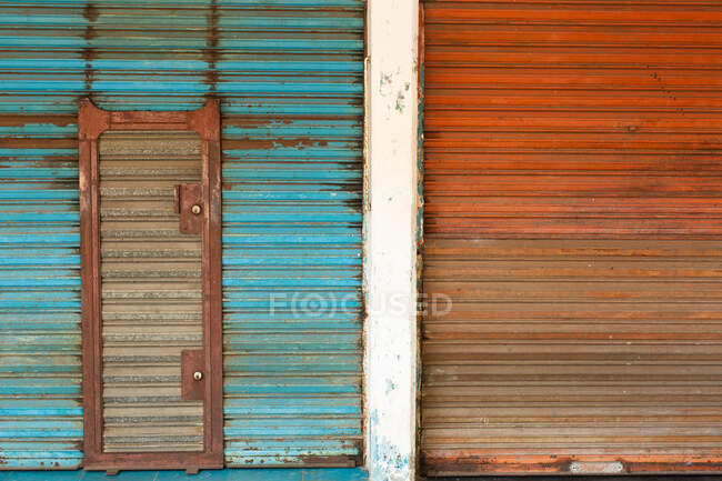 Weathered rusty metal shutter doors painted in blue and red color with shut doorway — Stock Photo