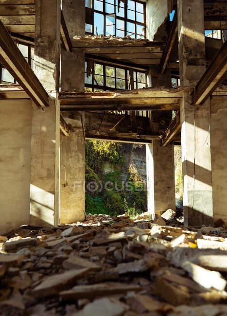 Bajo ángulo dentro de envejecido abandonado edificio de la ciudad interrumpido con basura en el suelo aligerado por los rayos del sol - foto de stock
