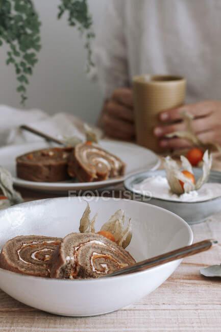 De cima de fatiado delicioso bolo de rolo doce caseiro com chantilly e Physalis flores secas servidas em prato em mesa de madeira com ingredientes — Fotografia de Stock