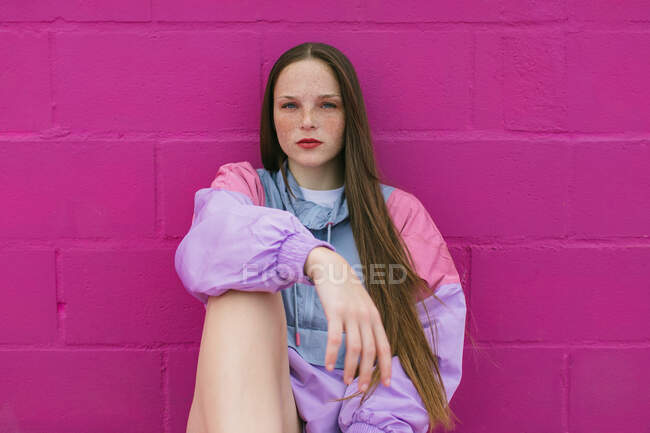 Trendy teenager sitting near pink wall — Stock Photo