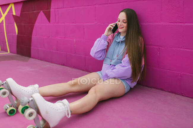 Cheerful young woman using smartphone on street — Stock Photo
