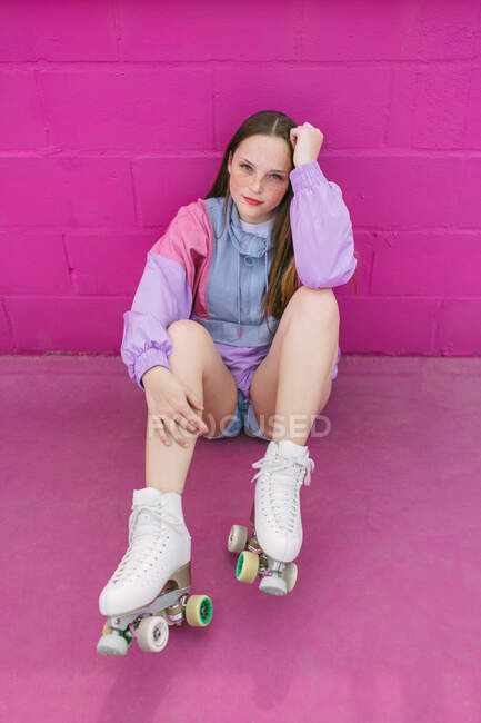 Trendy teenager with roller skates sitting near pink wall — Stock Photo