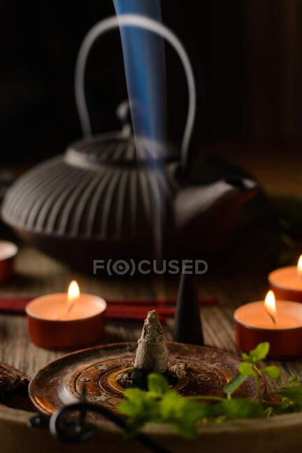 Состав горящего конуса ладана, чайника и свечей — стоковое фото