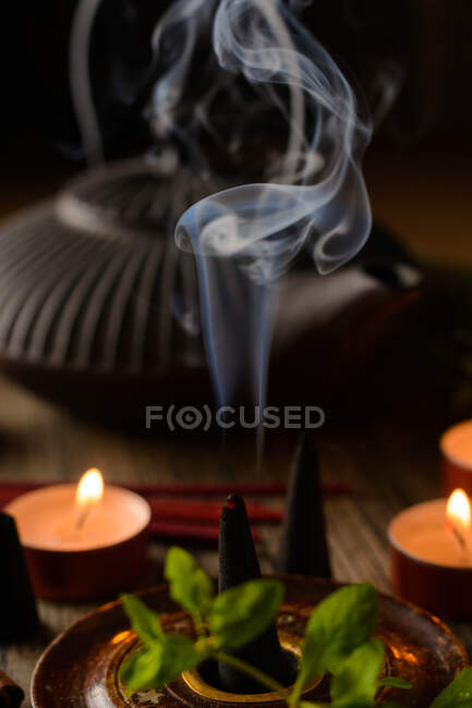 Composition of burning incense cone, teapot and candles — Stock Photo