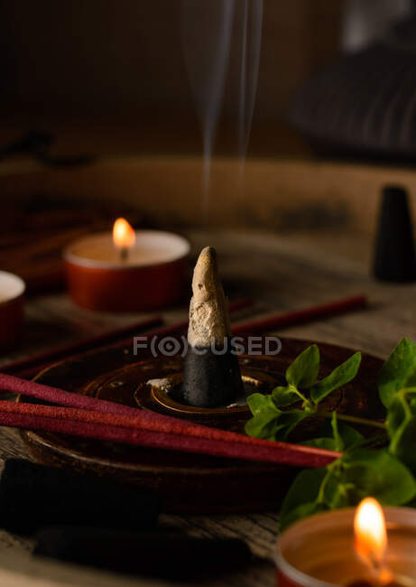 Composition of burning incense cone and candles — Stock Photo