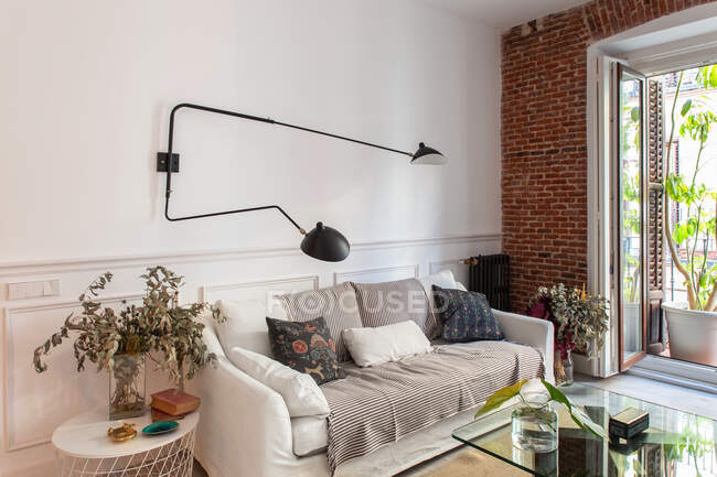 Cozy living room interior with sofa and brick wall — Stock Photo