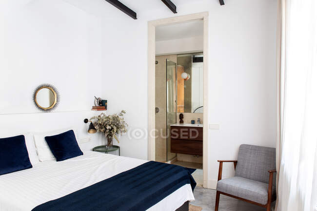 Comfortable bed with white and blue duvet and soft armchair located near bathroom doorway in cozy bedroom of modern apartment — Stock Photo
