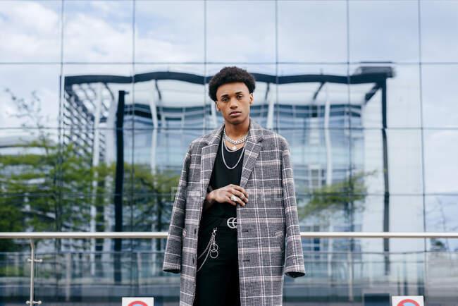 Уверенная молодая афроамериканская модель-подросток в модном тартановом пальто и стильных аксессуарах, смотрящая в камеру, стоя напротив современного здания со стеклянной стеной — стоковое фото