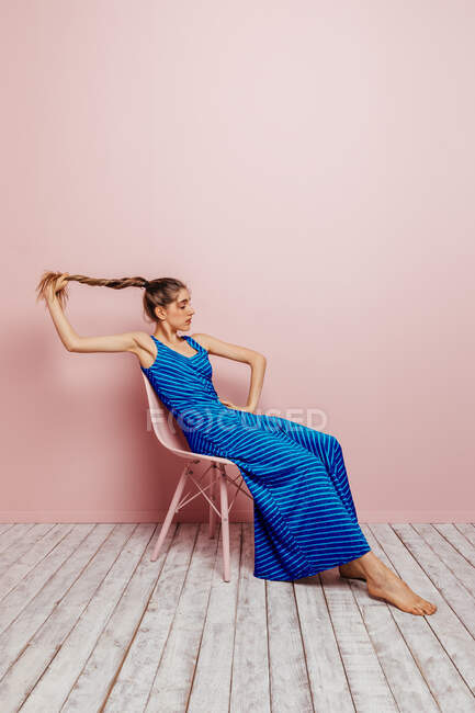 Side view of young woman in blue dress barefoot looking at camera holding ponytail while sitting in chair and looking away on minimalist pink background — Stock Photo