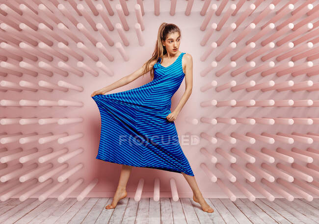 Young woman barefoot looking away stretching side of a blue dress while standing on tube hook pink background — Stock Photo