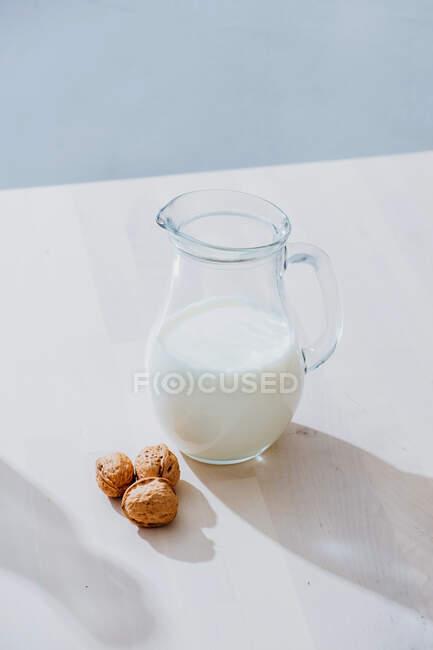 Vaso di latte e noci sul tavolo — Foto stock