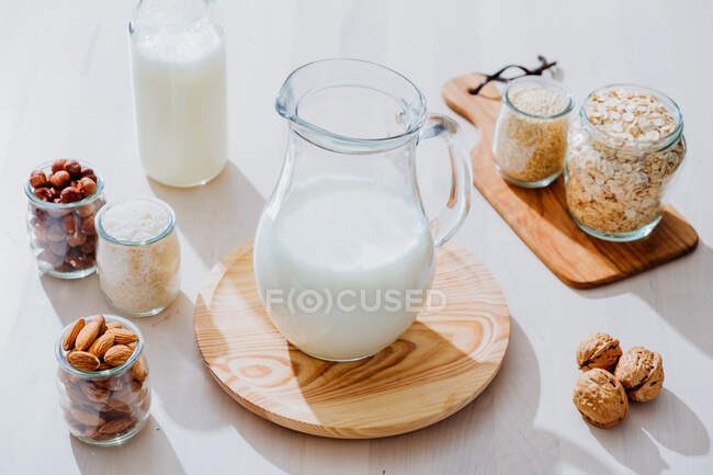 From above composition of glass jars with healthy vegan milk placed on table with various nuts and cereals — Stock Photo