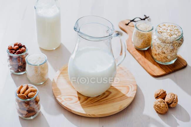 Сверху композиция из стеклянных банок со здоровым веганским молоком, выставленных на стол с различными орехами и орехами — стоковое фото