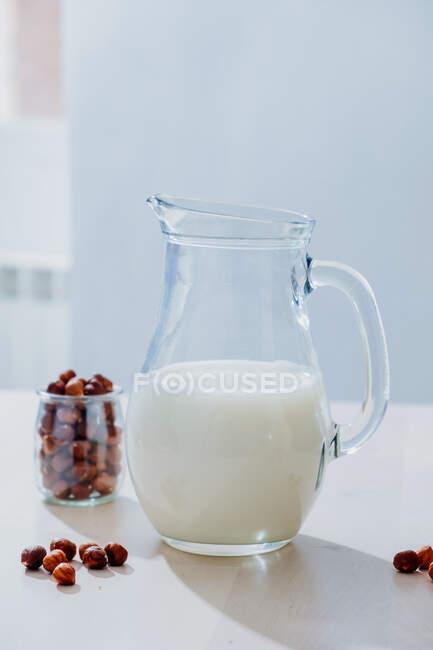 Glas Milch und Haselnüsse auf dem Tisch — Stockfoto