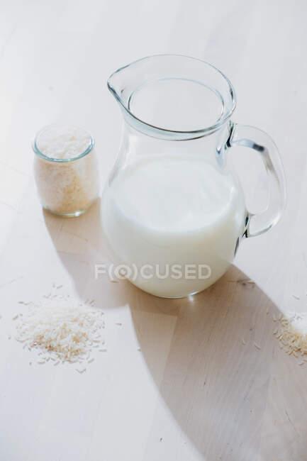 Pot de lait et de riz sur la table — Photo de stock