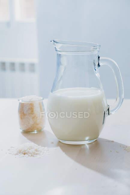 Баночка молока и риса на столе — стоковое фото