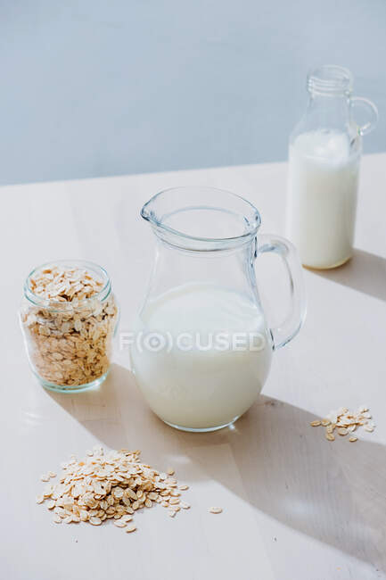 Jar of milk and oatmeal flakes on table — Stock Photo
