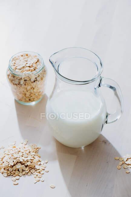 Dall'alto di vaso di vetro con latte d'avena vegan sano messo su tavolo di legno con pentola di fiocchi di farina d'avena — Foto stock