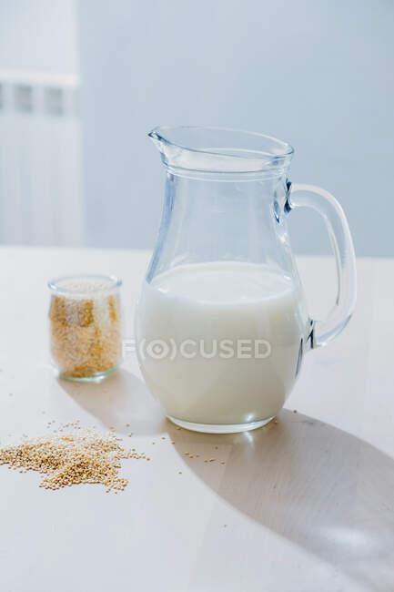 Банка молока и овсянка на столе — стоковое фото