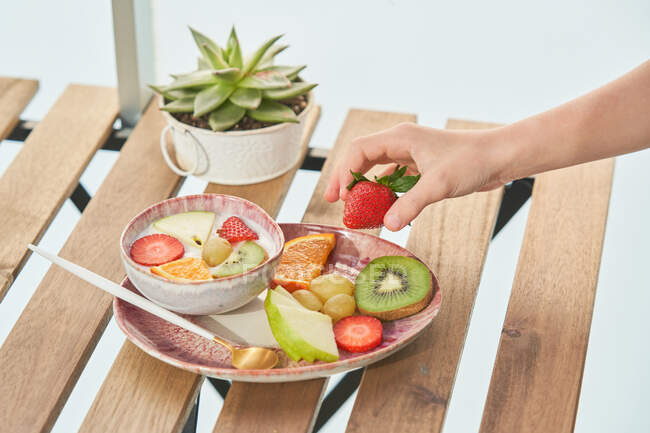 From above of crop unrecognizable female hands having healthy breakfast and eating delicious yogurt with sliced fresh assorted fruits served on wooden table — Fotografia de Stock