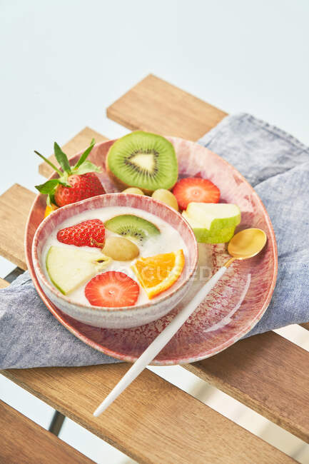 From above top view of tasty healthy breakfast with yogurt and assorted colorful fresh fruits served on wooden table — Stock Photo