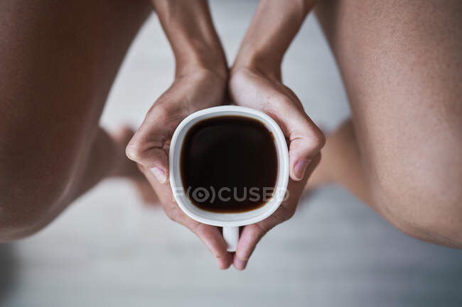 Top cropped view of woman holding cup of black coffee at home — стоковое фото